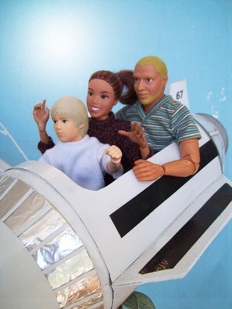Close-up photograph of three dolls sitting in a model version of the Rocket Jets ride in Disneyland