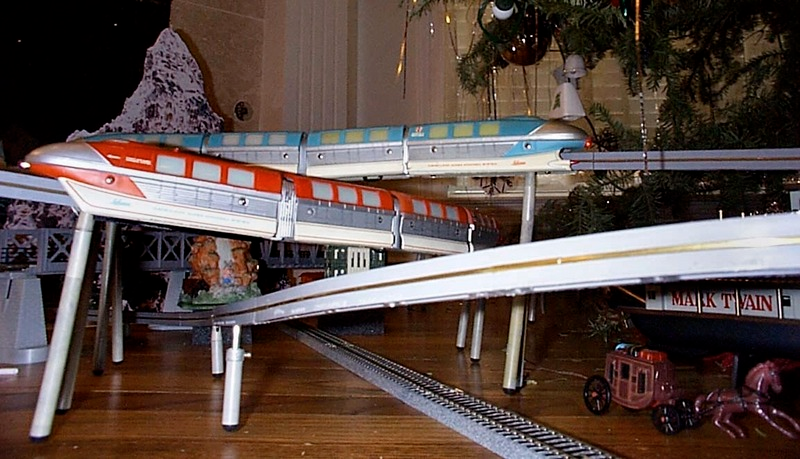Photograph of a toy version of the Disneyland-ALWEG monorail. The toy was produced by the company Schuco and features both blue and red trains. In this image, the toy is set up beneath a Christmas tree.